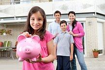 Kind steht mit Sparschwein vor seiner Familie